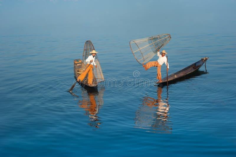 Pescador birmano en pescados de cogida del barco de bambú myanmar fotos de archivo