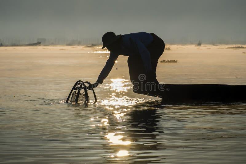 Pescador birmano en pescados de cogida del barco de bambú de la manera tradicional con la red hecha a mano fotos de archivo