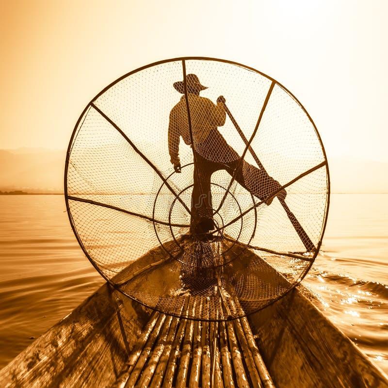 Pescador birmano en pescados de cogida del barco de bambú Lago Inle, Myanmar (Birmania) fotografía de archivo