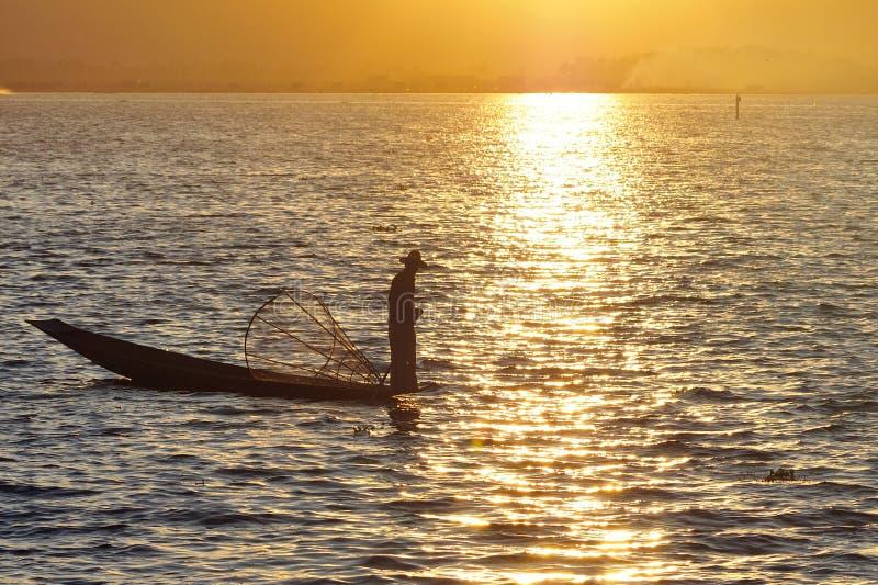 Pescador birmano en pescados de cogida del barco de la manera tradicional en el lago Inle, Myanmar imagen de archivo