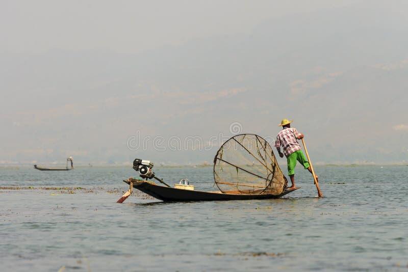 Pescador birmano no identificado en pescados de cogida del barco de bambú de la manera tradicional con la red hecha a mano imagenes de archivo