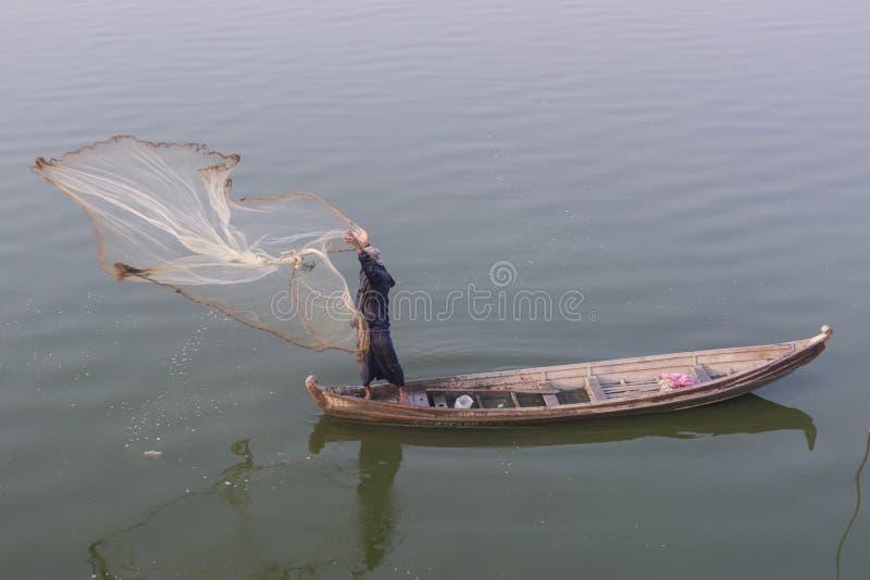 Pescador birmano que lanza una red de pesca en el lago Taungthaman, Birmania foto de archivo