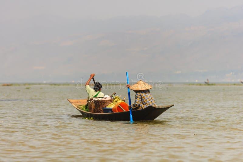 Pescador burmese não identificado em peixes de travamento do barco de bambu na maneira tradicional com rede feito a mão foto de stock