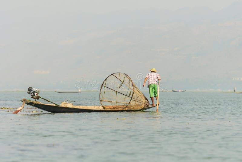 Pescador burmese não identificado em peixes de travamento do barco de bambu na maneira tradicional com rede feito a mão fotos de stock royalty free