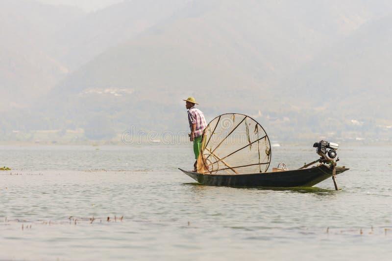 Pescador burmese não identificado em peixes de travamento do barco de bambu na maneira tradicional com rede feito a mão imagem de stock royalty free