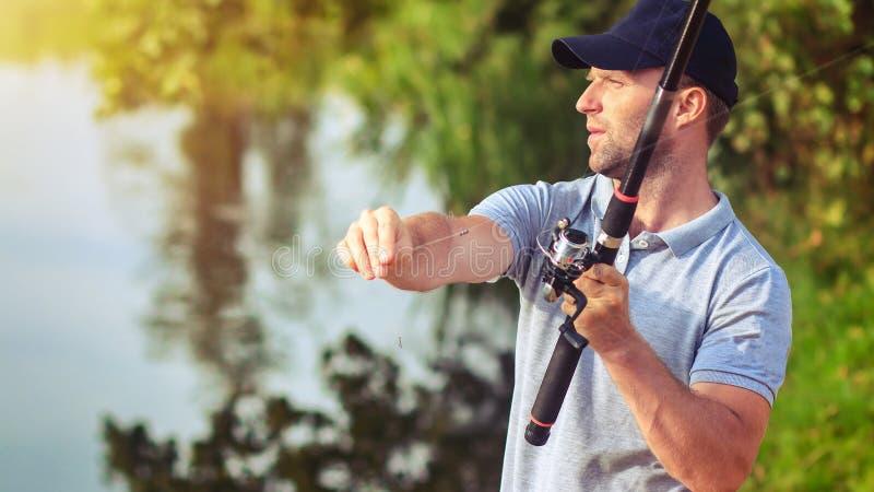 Pescador com haste de pesca O pescador mantém o equipamento de pesca Pesca no rio Retrato do pescador Atividades exteriores ativa imagens de stock