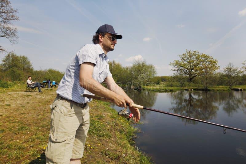 Pescador com a haste na mão imagem de stock