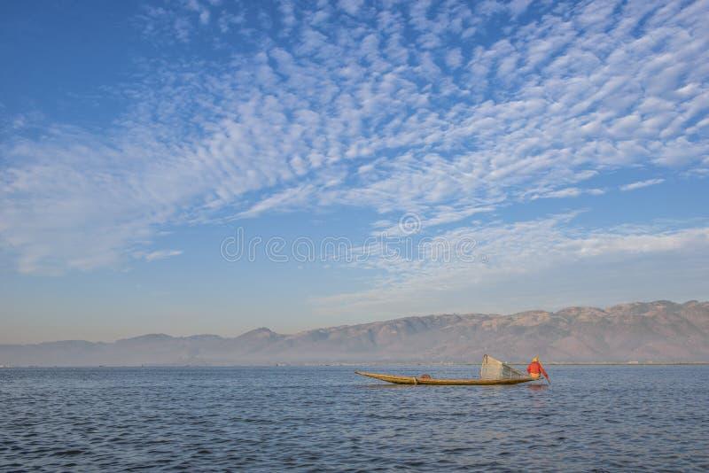 Pescador com o céu azul no lago fotografia de stock royalty free