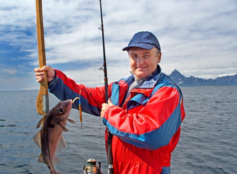 Pescador com um peixe no console de Lofoten fotos de stock royalty free