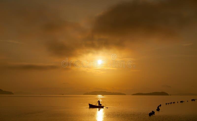 Pescador com uma pá no bote no mar tropical com b fotos de stock royalty free