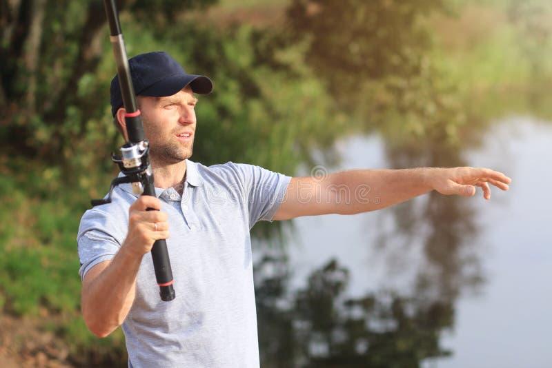 Pescador com a vara de pesca na costa do lago Capturas do homem dos peixes no rio Atividade de lazer Passatempo no ar livre Caçad fotos de stock royalty free