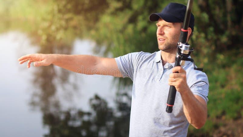 Pescador com a vara de pesca no rio Caçador dos peixes Passatempo ativo Peixes da captura do homem no lago fotos de stock royalty free