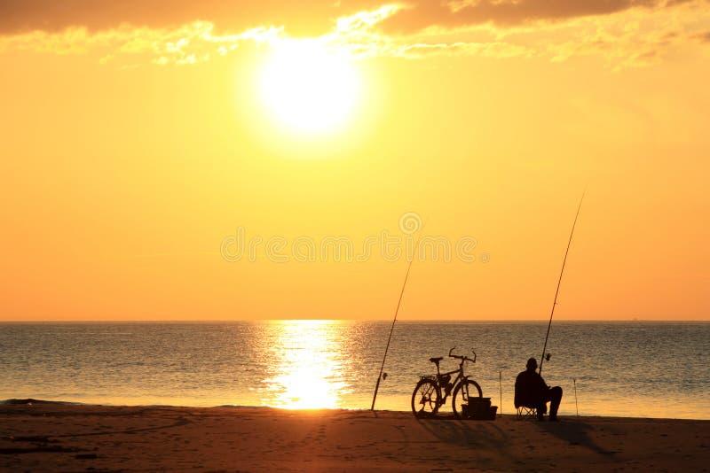 Pescador con la pesca de la bici en la playa imagen de archivo libre de regalías
