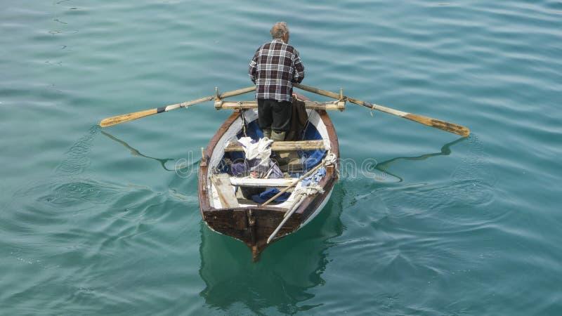 Pescador con su barco imagen de archivo