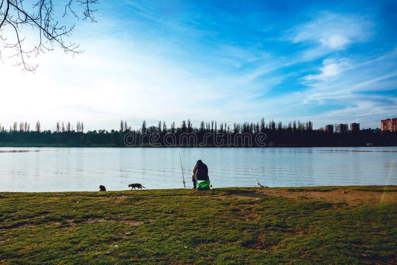 Pescador con una caña de pescar en la orilla del río gatos Cielo azul imagen de archivo libre de regalías