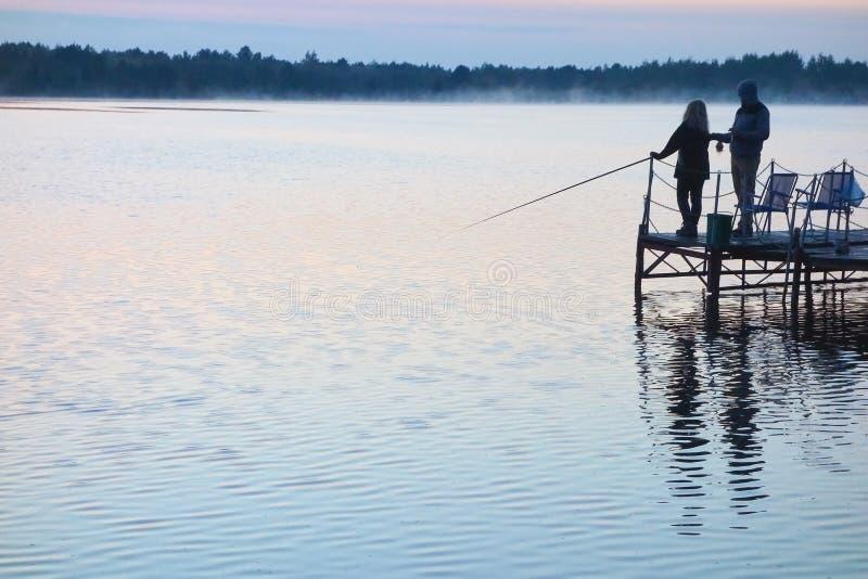 Pescador con una muchacha que pesca en un lago en la puesta del sol imágenes de archivo libres de regalías