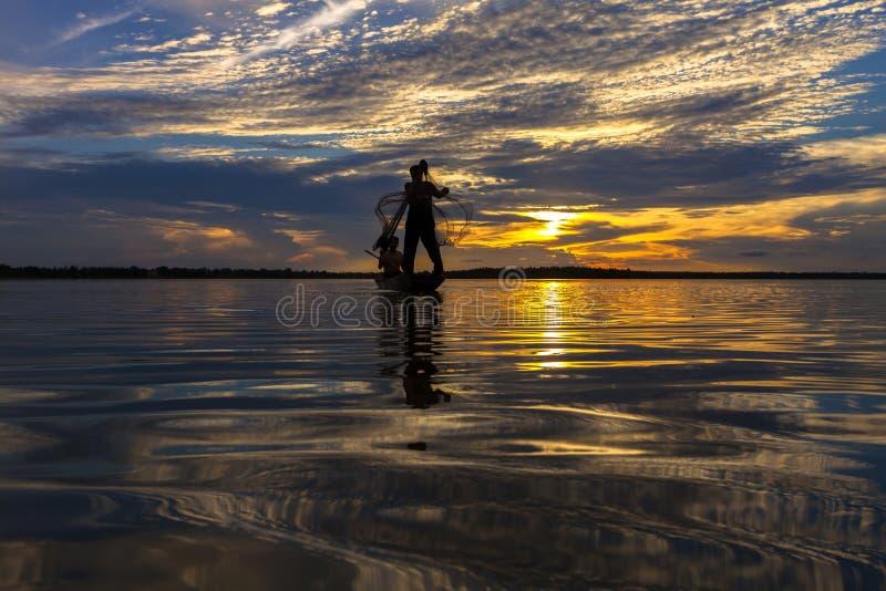 Pescador de la silueta con la red en el lago foto de archivo libre de regalías