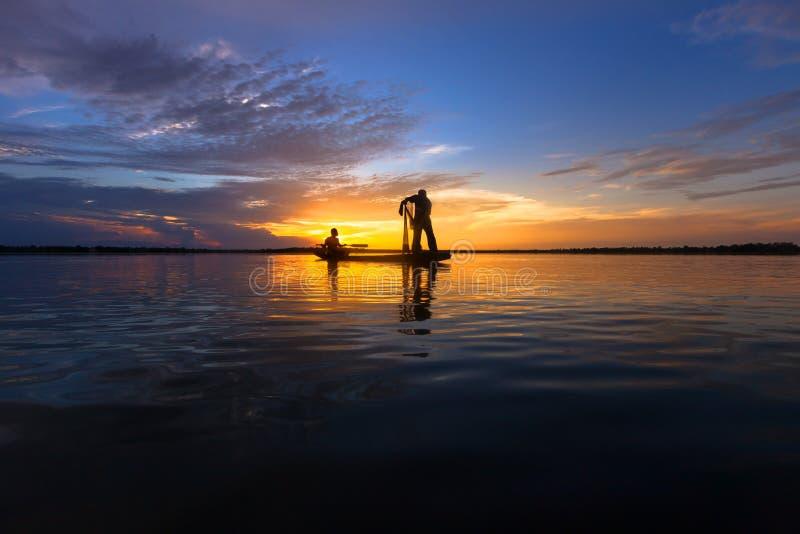 Pescador de la silueta con la red en el lago imagenes de archivo