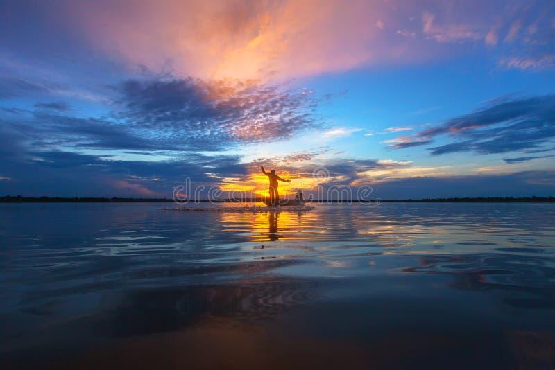Pescador de la silueta con la red en el lago imágenes de archivo libres de regalías