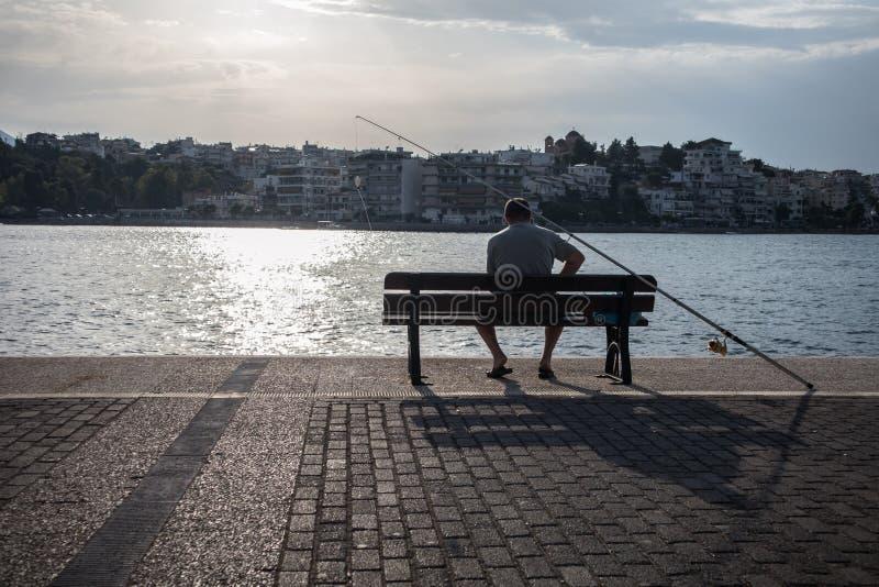 Pescador de servicio, en una ciudad costera en Grece imagenes de archivo