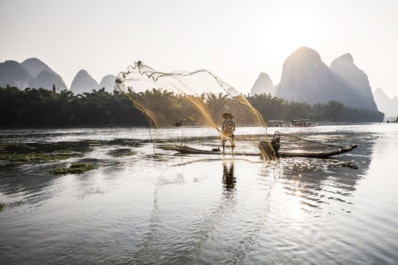 Pescador do cormorão que joga uma rede fotos de stock