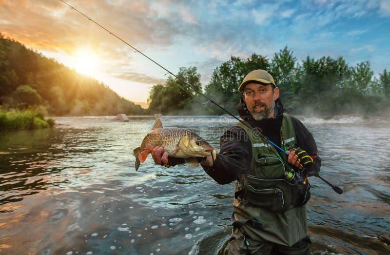 Pescador do esporte que guarda peixes do troféu Pesca exterior no rio imagens de stock royalty free