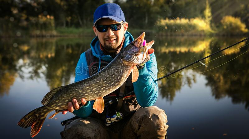 Pescador e troféu grande Pike foto de stock
