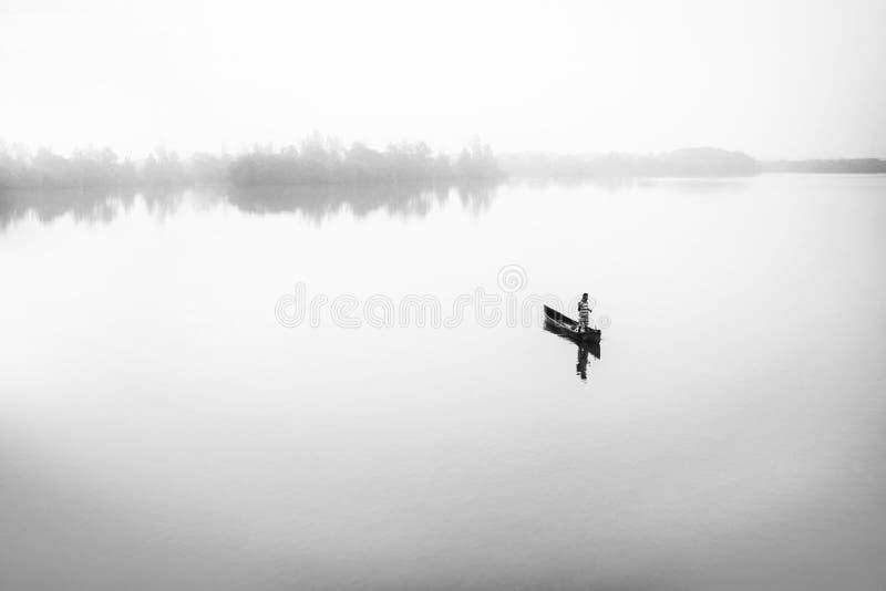 Pescador em seu barco em um rio imagens de stock royalty free