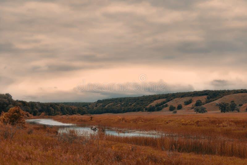 Pescador em um barco em um lago pequeno em um vale montanhoso nebuloso foto de stock