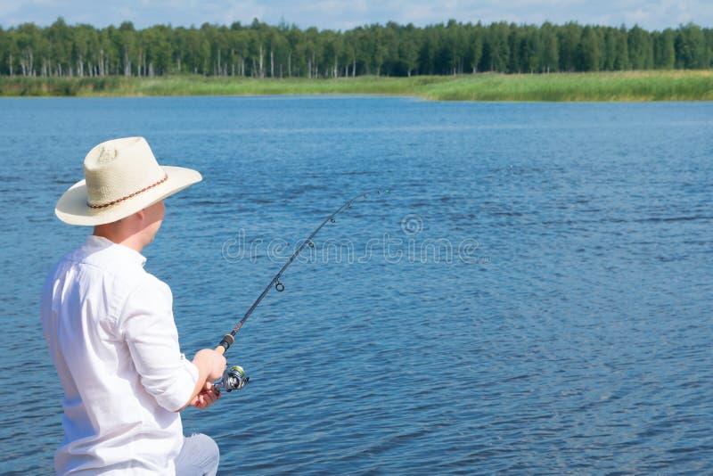 Pescador em um chapéu, mantendo uma vara de pesca, contra a água e o céu azul, vista traseira, há um lugar para a inscrição imagem de stock