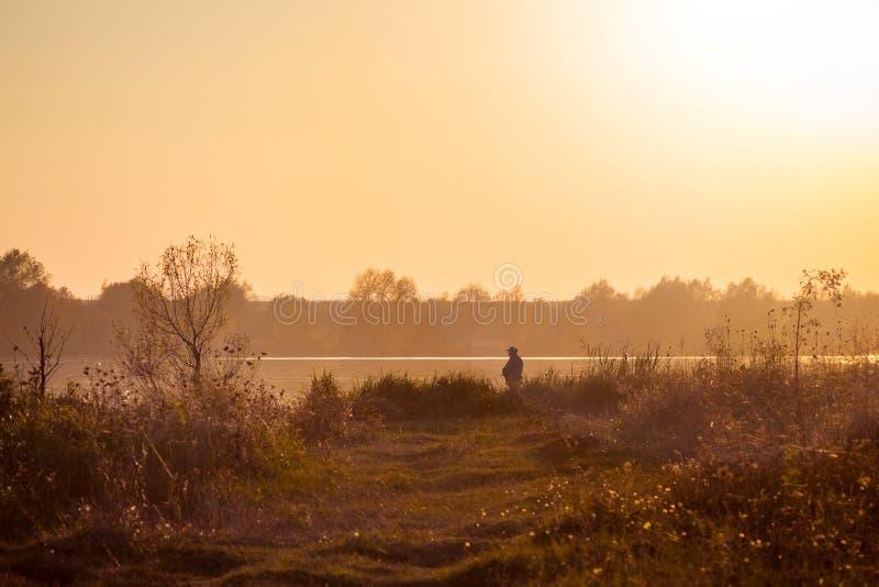 Pescador en el banco del río durante el sunset_ imágenes de archivo libres de regalías