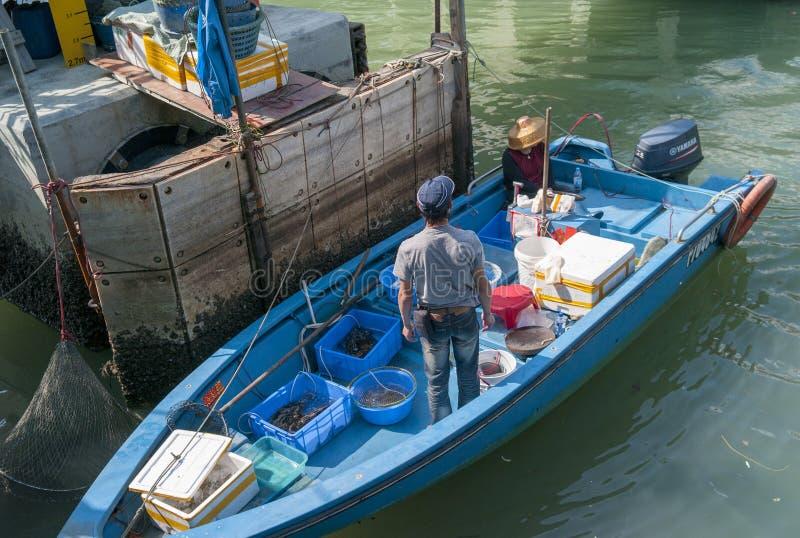 Pescador en el barco en Hong Kong imagenes de archivo