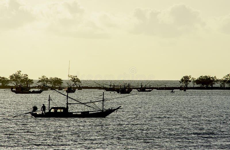 Pescador en el barco y los barcos de pesca parqueados en la costa costa del mar en la playa thian de Laem, Chumphon en Tailandia fotografía de archivo libre de regalías