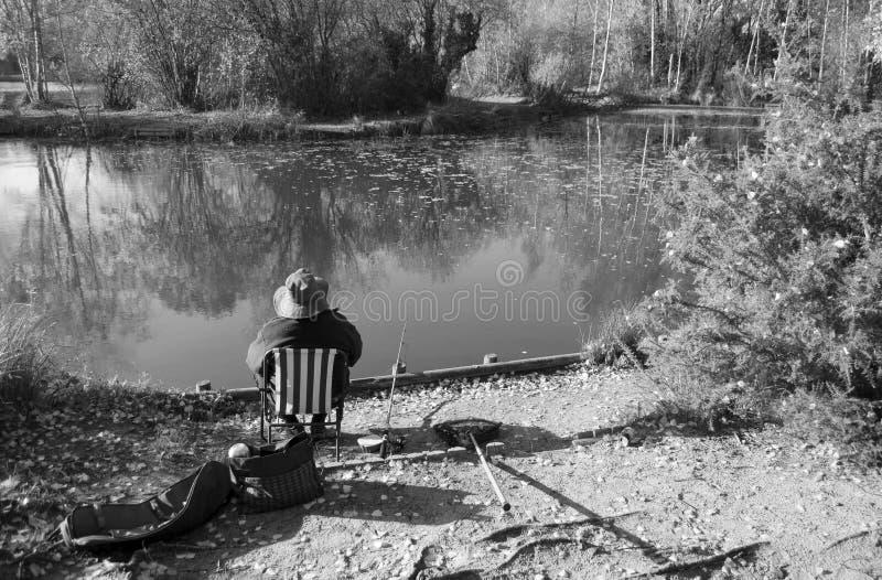 Pescador en el lago que se sienta cómodamente en el suyo en una silla, aguas del arbolado Grantham Reino Unido Fotografía blanco  fotos de archivo