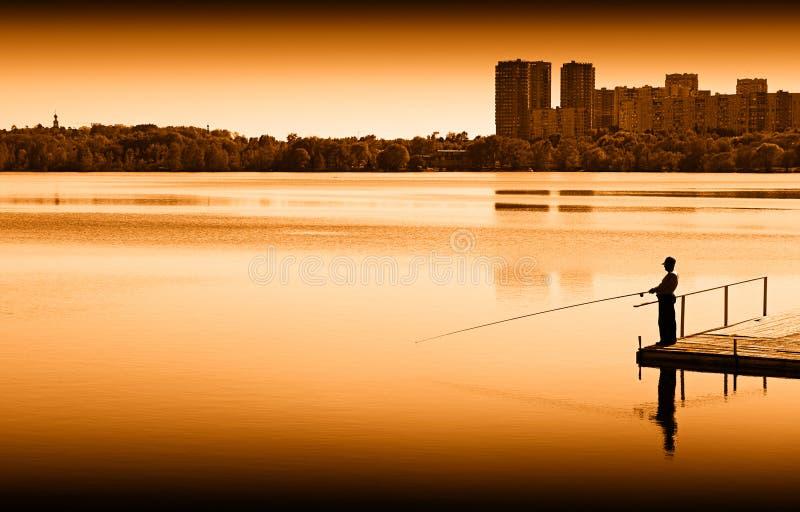 Pescador en fondo del scape de la ciudad del muelle del río fotos de archivo libres de regalías