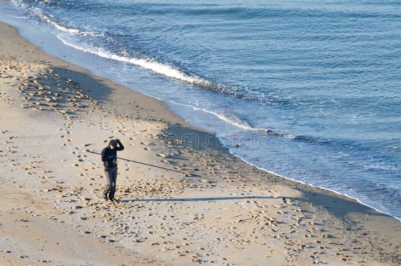 Pescador en la playa imagenes de archivo