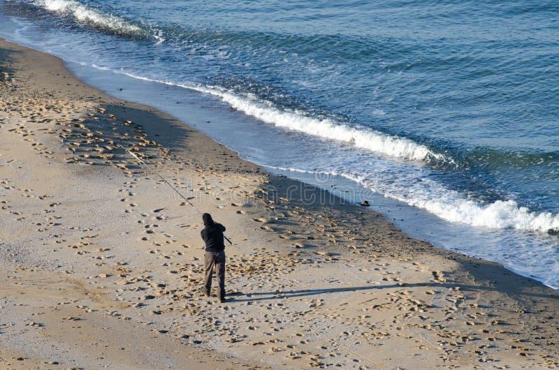Pescador en la playa fotos de archivo