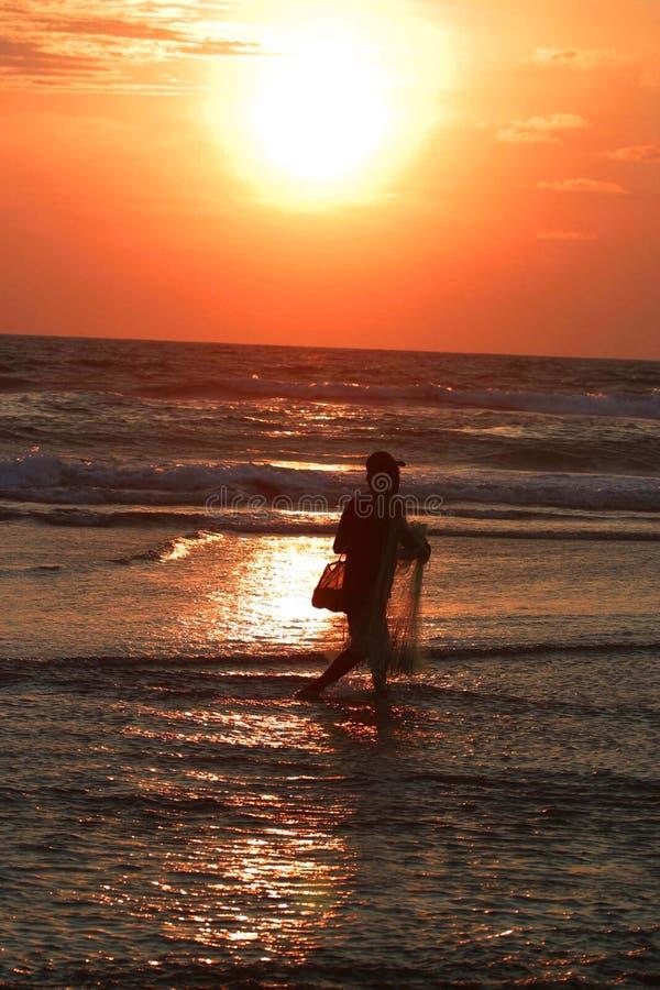 Pescador en la puesta del sol imagen de archivo libre de regalías