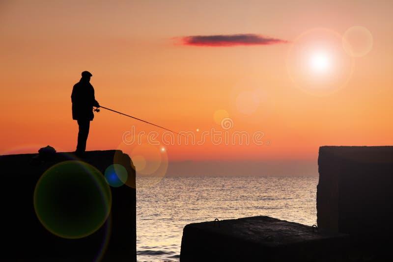 Pescador en la salida del sol imagen de archivo