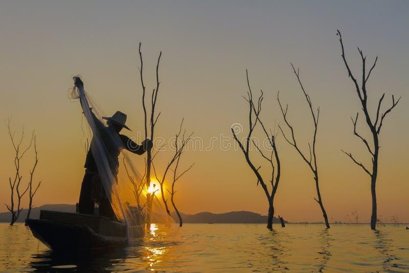 Pescador en un barco de madera con el fondo de la puesta del sol fotografía de archivo libre de regalías