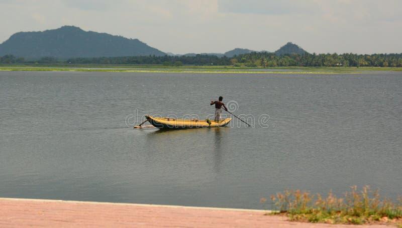 Pescador en un barco tradicional Lago Kataragama Sri Lanka imagen de archivo