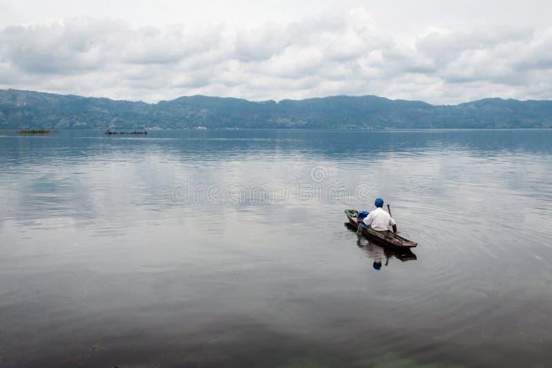 Pescador en un bote pequeño con sus trampas en el lago más grande adentro fotografía de archivo libre de regalías