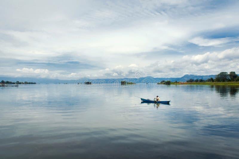 Pescador en un bote pequeño con sus trampas en el lago más grande adentro imágenes de archivo libres de regalías