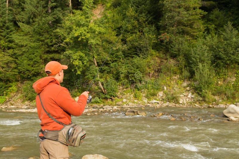 Pescador en un río de la montaña fotografía de archivo