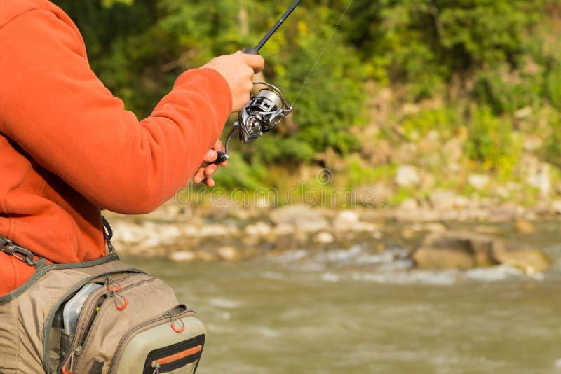 Pescador en un río de la montaña imagen de archivo