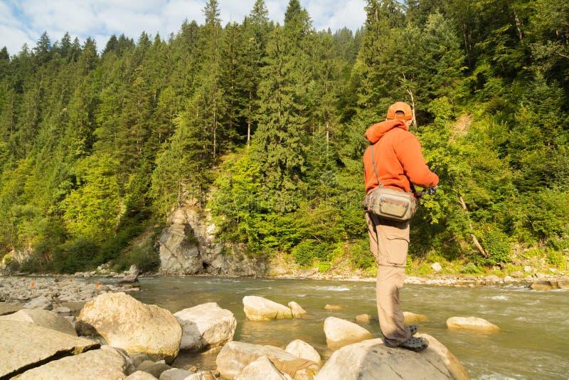 Pescador en un río de la montaña foto de archivo