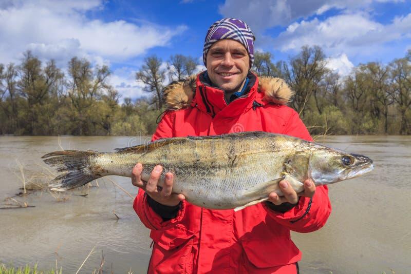 Pescador feliz com peixes grandes pesca Vara dos peixes fotografia de stock royalty free