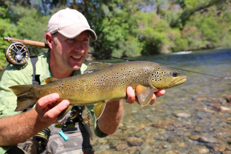 Pescador feliz con la trucha marrón cogida foto de archivo