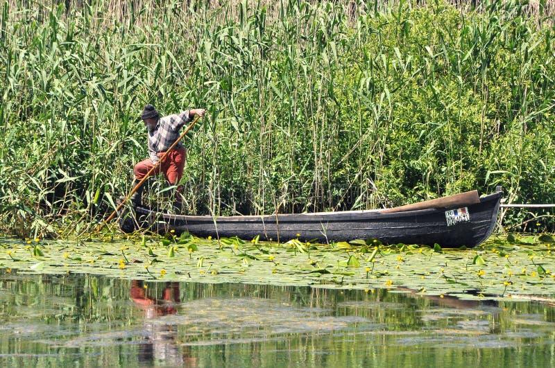 Pescador idoso em seu barco imagens de stock royalty free