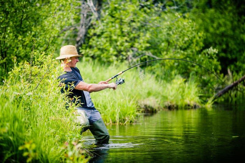 Pescador joven Catching un pescado grande foto de archivo libre de regalías